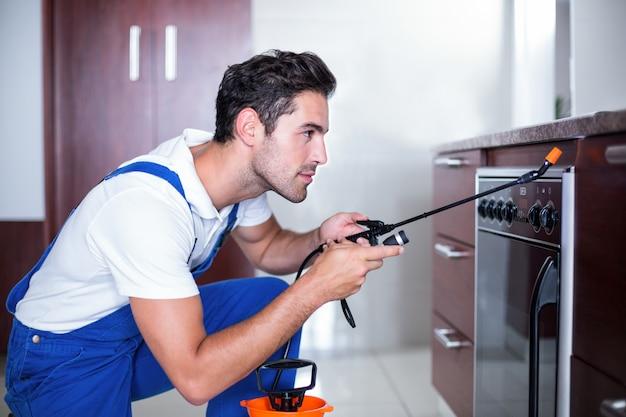 Hombre rociando insecticida en horno