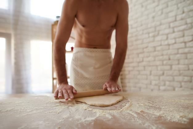 Hombre con el rodillo que desarrolla la pasta en la tabla de cocina.
