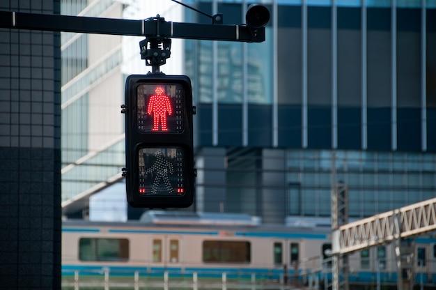 Hombre rojo detener la señal de tráfico en frente de la estación de tren de tokio