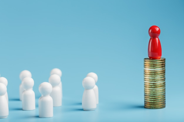 El hombre rojo se para en dinero y monedas de oro y controla una multitud de personas blancas. el concepto de poder codicioso y gestión de personas.