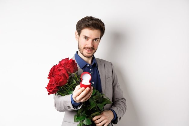 Hombre romántico con boquet de rosas rojas pidiendo casarse con él, sosteniendo el anillo de compromiso y mirando confiado a la cámara, de pie en traje sobre fondo blanco.