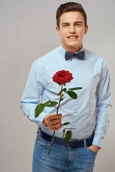 Hombre romántico con rosa roja y traje de pantalón de camisa ligera.