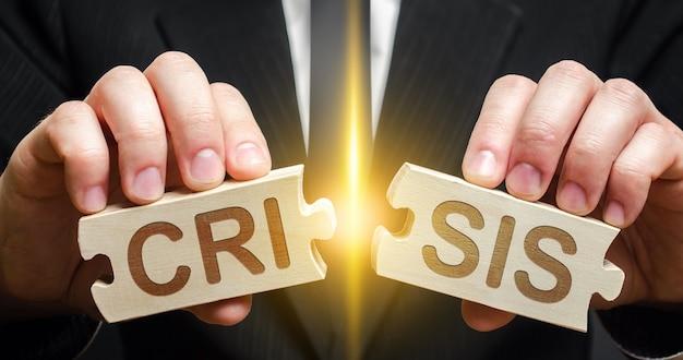 El hombre rompe dos rompecabezas con la palabra crisis. evitar o poner fin a la crisis política económica.