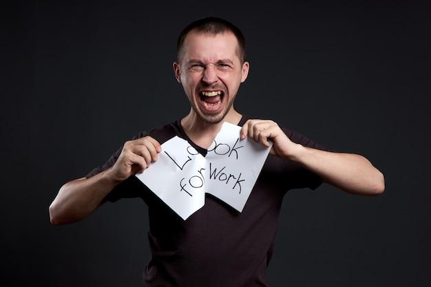 Hombre rompiendo un papel con las palabras buscar trabajo