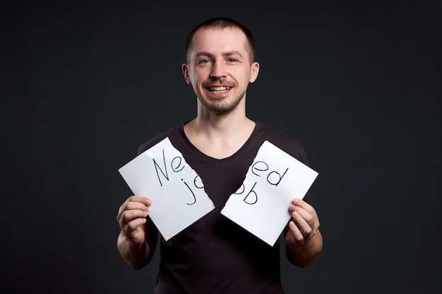 Hombre rompiendo un papel con las palabras necesita trabajo