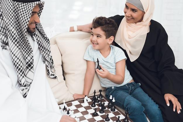 Un hombre en ropa árabe juega al ajedrez con un niño pequeño.
