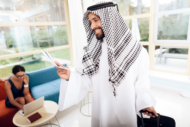 Un hombre en ropa árabe está sosteniendo una maleta.