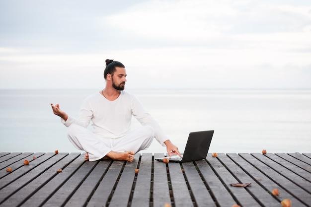 Hombre en ropa blanca meditando yoga con portátil en el muelle de madera