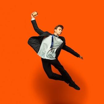 Hombre en ropa casual de estilo de oficina saltando aislado en la pared