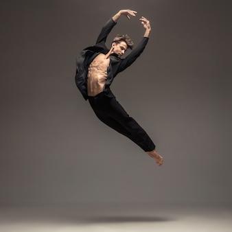 Hombre en ropa casual de estilo de oficina saltando y bailando aislado en gris