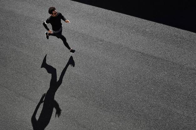 Hombre en ropa deportiva corriendo en la carretera