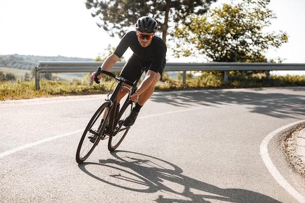 Hombre en ropa deportiva montando bicicleta entre campo