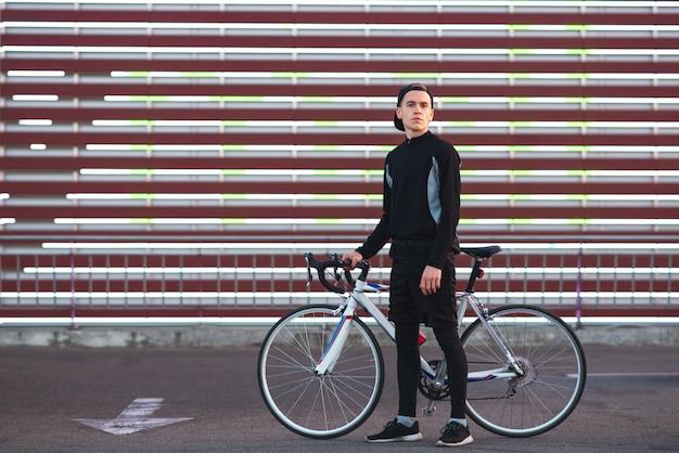 Hombre en ropa deportiva oscura y con una bicicleta se encuentra en el fondo rayado de la pantalla grande y mira a la cámara.