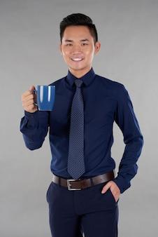 Hombre ropa formal azul oscuro de pie contra el fondo gris con azul marino taza de té