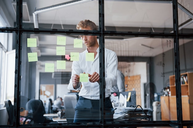 El hombre con ropa formal se encuentra en la oficina detrás del vidrio y le pone pegatinas.