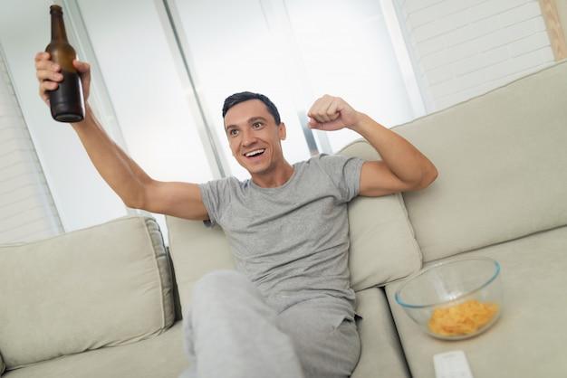Hombre en ropa gris casa está sentado en el sofá y descansando.