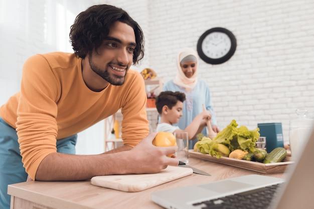 Un hombre en ropa moderna en la cocina con un ordenador portátil.