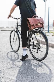 Hombre en ropa negra que monta la bicicleta en el camino