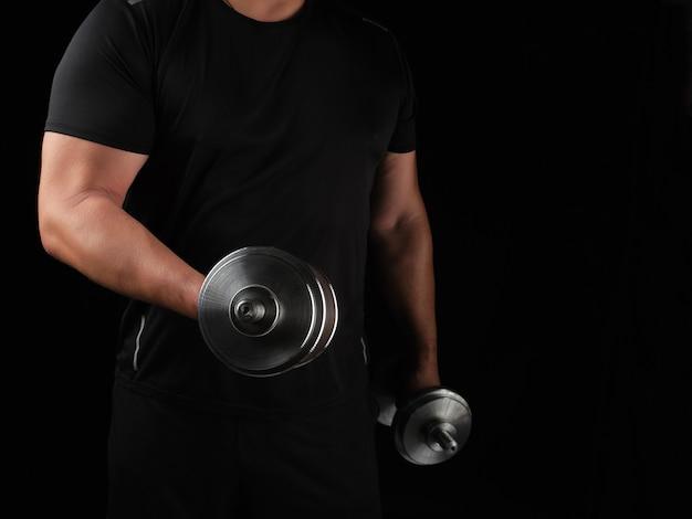 Hombre en ropa negra tiene pesas de acero en sus manos