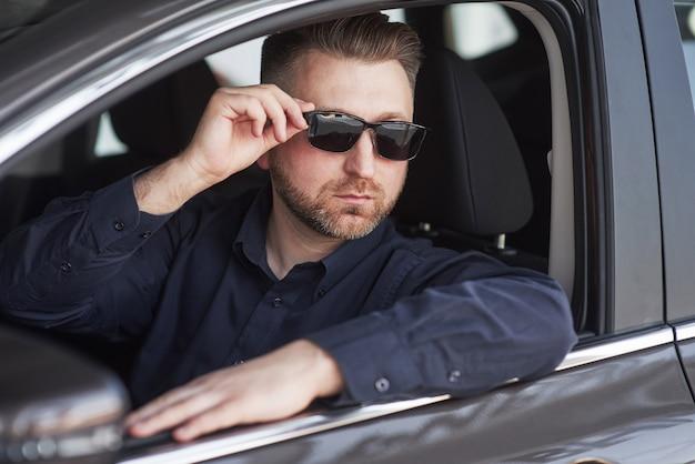 Hombre en ropa oficial probando su nuevo coche en el salón del automóvil