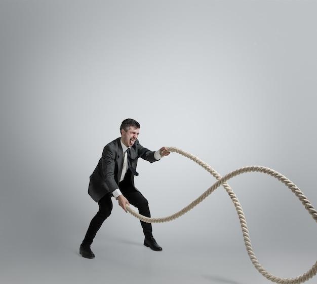 Hombre en ropa de oficina entrenando con cuerdas sobre fondo gris.