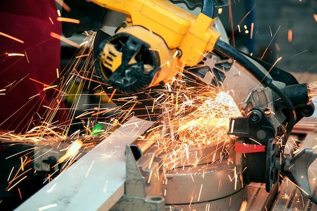Hombre en ropa ordinaria y gafas protectoras con amoladoras angulares mientras trabaja.