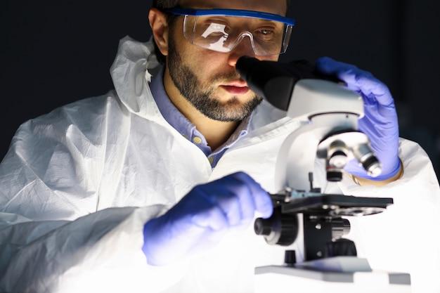 Hombre en ropa protectora examina microscopio