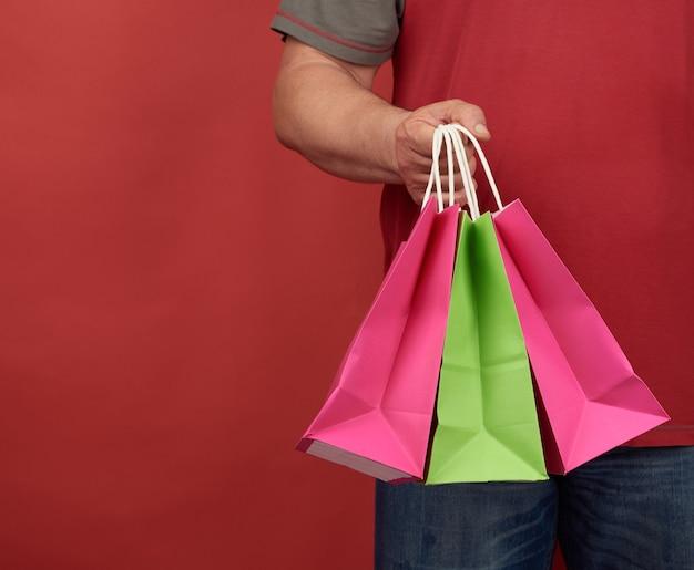 El hombre con ropa roja tiene una pila de bolsas de papel blanco, espacio rojo, concepto de compras y entrega de pedidos