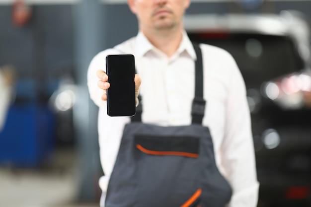 Hombre en ropa de trabajo mostrando gadget