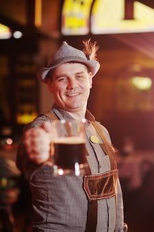 Hombre en ropa tradicional bávara en el oktoberfest con una cerveza en la mano