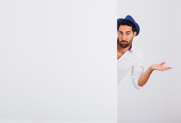 Hombre en ropa de verano detrás de puerta haciendo signo de no lo sé