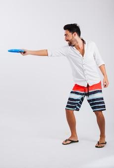 Hombre en ropa de verano con frisbee