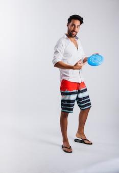 Hombre en ropa de verano mostrando frisbee