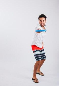 Hombre en ropa de verano sujetando frisbee