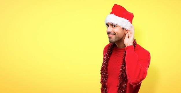 Hombre con ropas rojas celebrando las fiestas navideñas escuchando algo.