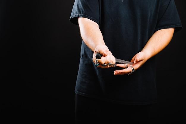 Hombre sin rostro posando con daga