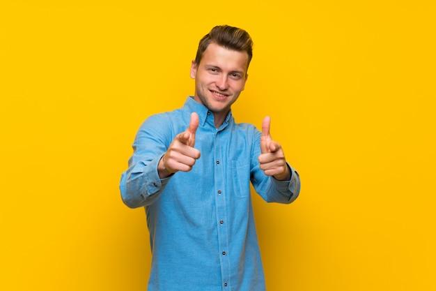 Hombre rubio aislado en la pared amarilla que señala al frente y sonriendo