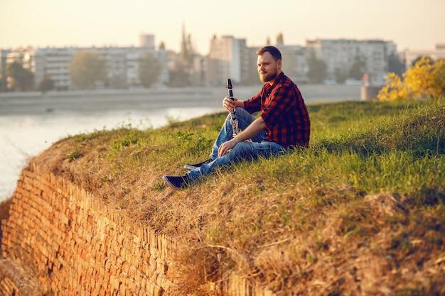 Hombre rubio barbudo caucásico hermoso que se sienta en el acantilado con el clarinete en manos y que mira hermosa vista.