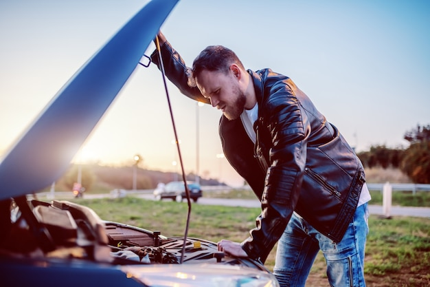 Hombre rubio barbudo caucásico hermoso serio joven en la chaqueta de cuero que busca el motor de su coche debajo del capó. algo salió mal.