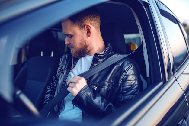 Hombre rubio barbudo caucásico joven en chaqueta de cuero sentado en su coche moderno y abrocharse el cinturón de seguridad. seguridad primero.