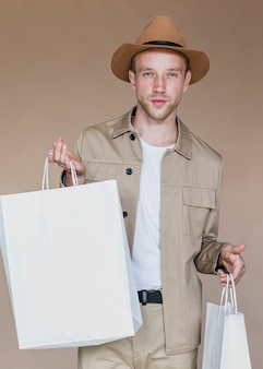 Hombre rubio con bolsas de compras mirando a la cámara