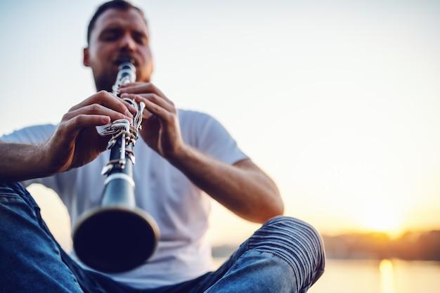 Hombre rubio caucásico barbudo hermoso joven que se sienta en el acantilado y que toca el clarinete.