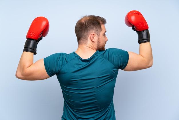 Hombre rubio deporte sobre pared azul con guantes de boxeo