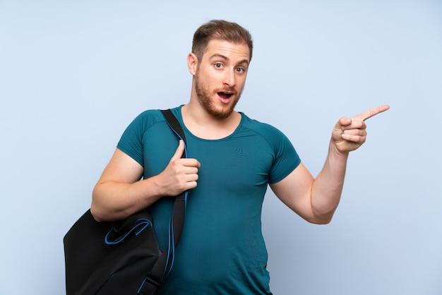 Hombre rubio deporte sobre pared azul sorprendido y apuntando con el dedo a un lado