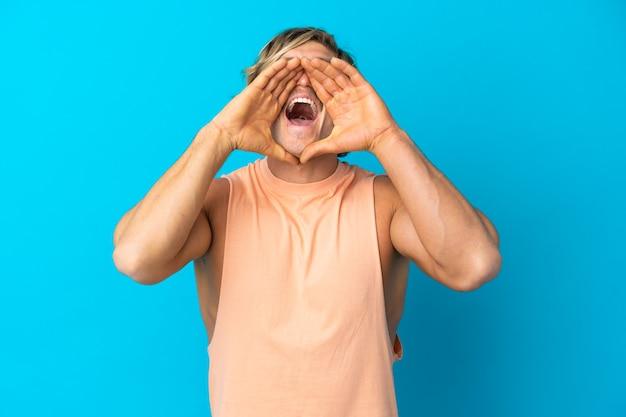 Hombre rubio guapo aislado en la pared azul gritando y anunciando algo