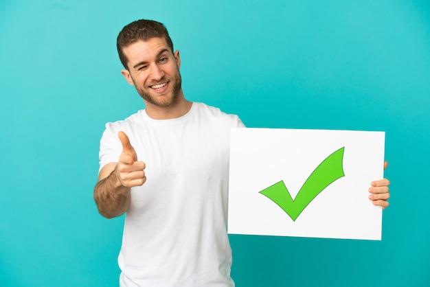Hombre rubio guapo sobre fondo azul aislado sosteniendo un cartel con el icono de marca de verificación verde de texto y apuntando hacia el frente