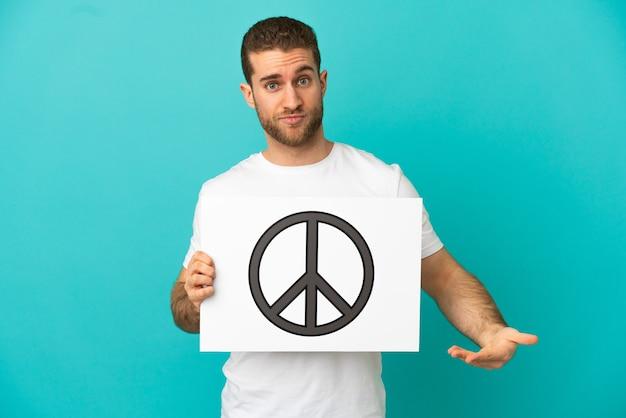 Hombre rubio guapo sobre fondo azul aislado sosteniendo un cartel con el símbolo de la paz y apuntando