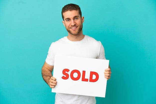 Hombre rubio guapo sobre fondo azul aislado sosteniendo un cartel con texto vendido con expresión feliz