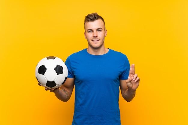 Hombre rubio hermoso joven que sostiene un balón de fútbol sobre fondo amarillo aislado que señala una gran idea