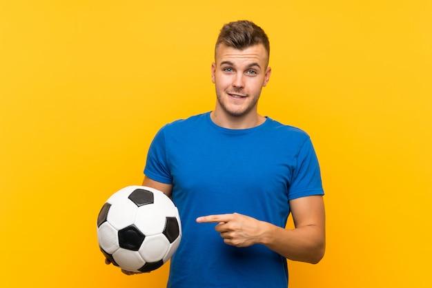 Hombre rubio hermoso joven que sostiene un balón de fútbol sobre la pared amarilla aislada y que lo señala